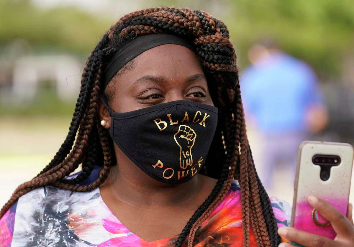 Mary Courtney takes a video during a protest about a Black Lives Matter billboard in parking lot at 11107 Bellaire Blvd. Saturday, July 11, 2020, in Houston. The Vietnamese Community of Houston and Vicinity organization had scheduled a protest and forum at the site.