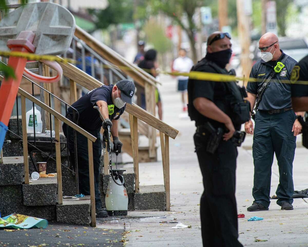 An Albany fire fighter washes down a porch on Second Street, the site of the citya€™s most recent shooting on Saturday, July 11, 2020. According to police, an 18-year-old male was shot in the leg and taken to Albany Medical Center Hospital for treatment of non-life threatening injuries. (Jim Franco/special to the Times Union.)