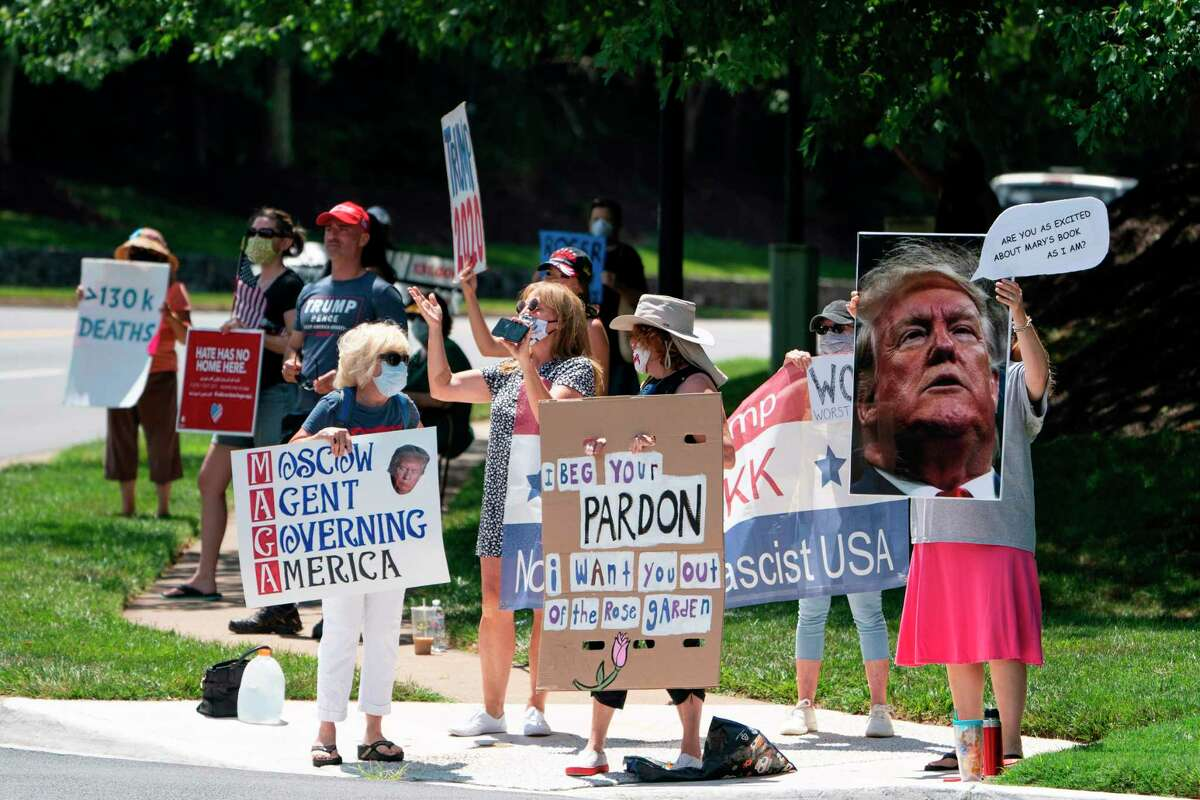 Demonstrators against and supporters for US President Donald Trump hold signs as Trump departs his Trump National Golf Club, on July 11, 2020 in Sterling, Virginia. - Trump on June 10 commuted the prison sentence of his longtime ally Roger Stone, shielding the veteran Republican operative from 40 months behind bars. (Photo by Alex Edelman / AFP) (Photo by ALEX EDELMAN/AFP via Getty Images)