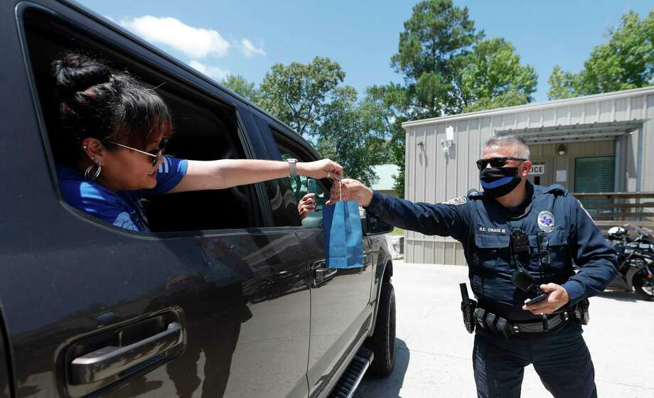 Oak Ridge patrol officer Ralph Craig III gets a back of cookies from a resident during a parade in support of various law enforcement agencies in Montgomery County, Saturday, July 11, 2020, in Oak Ridge. Photo: Jason Fochtman, Houston Chronicle / Staff Photographer / 2020 © Houston Chronicle