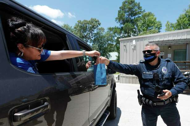 Oak Ridge patrol officer Ralph Craig III gets a back of cookies from a resident during a parade in support of various law enforcement agencies in Montgomery County, Saturday, July 11, 2020, in Oak Ridge.
