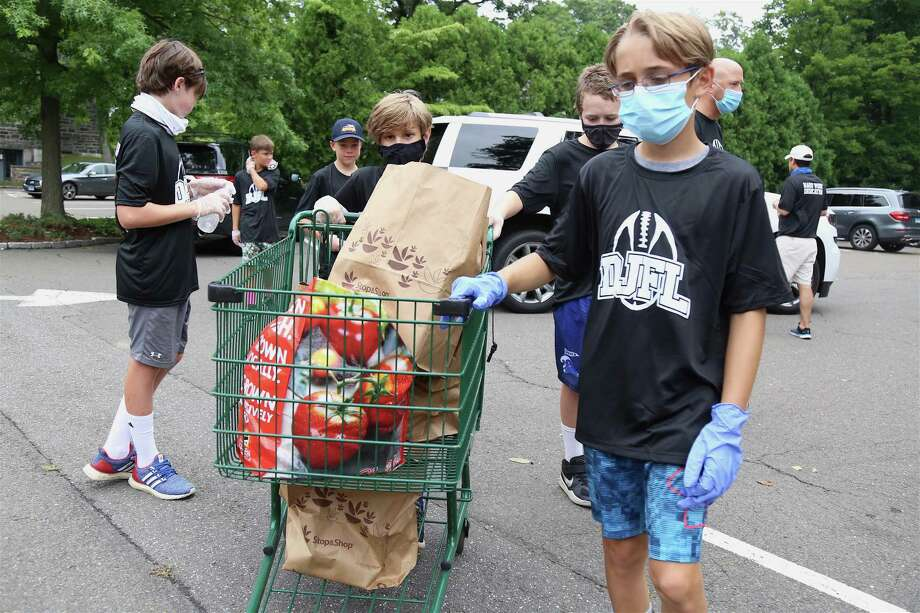 Liam Bortel, 11, leads a cart full of groceries back to the storage bin. The Darien Junior Football League held a drive-thru food drive on Saturday to benefit Person-to-Person. Photo: Jarret Liotta /Hearst Connecticut Media /