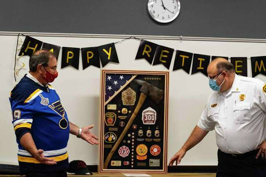Chief Richard Welle stands back as he listens to Dep. Fire Chief James Whiteford explain what each item in a parting gift means. Photo: Tyler Pletsch | Intelligencer