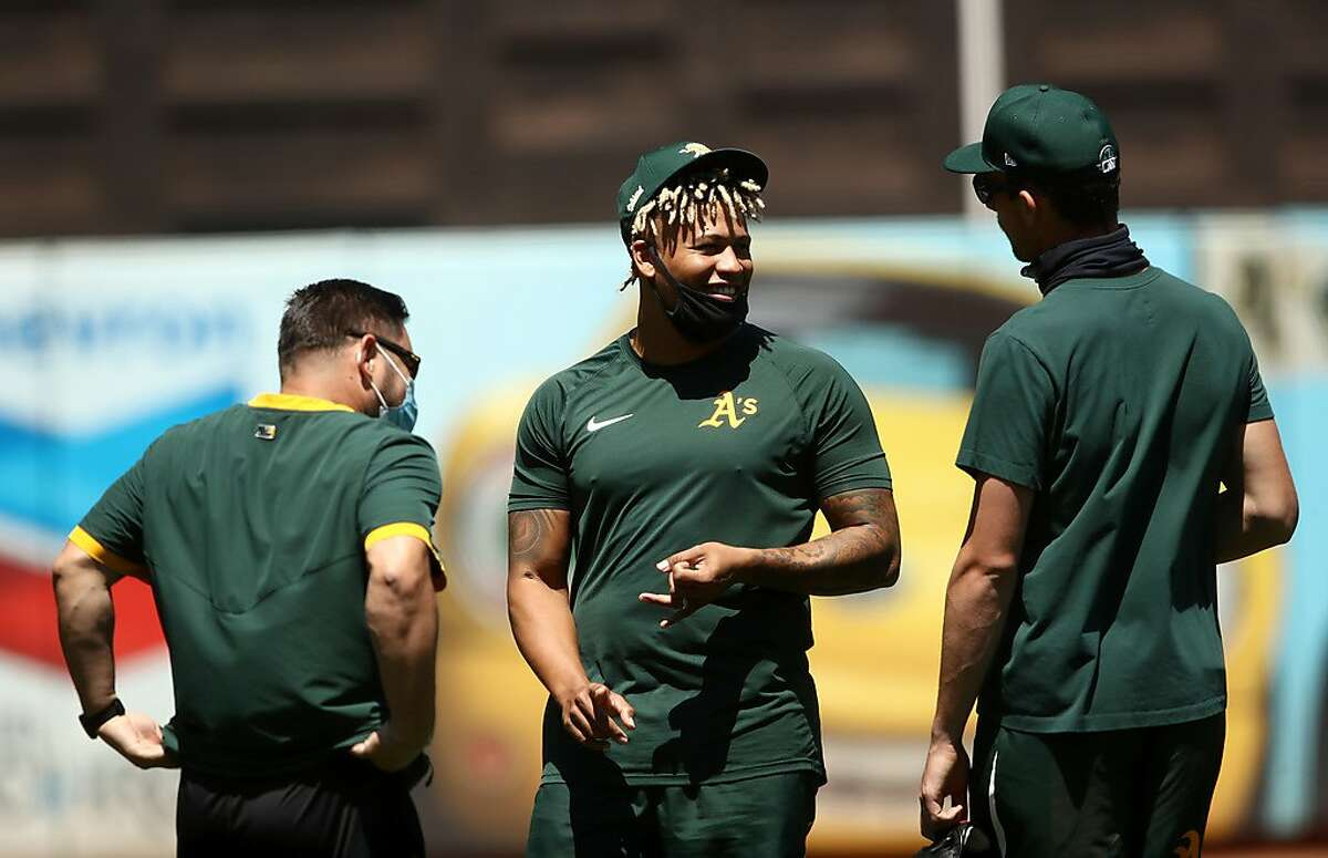 OAKLAND, CALIFORNIA - JULY 05: Frankie Montas #47 (center) of the Oakland Athletics speaks with teammates during summer workouts at RingCentral Coliseum on July 05, 2020 in Oakland, California. (Photo by Ezra Shaw/Getty Images)