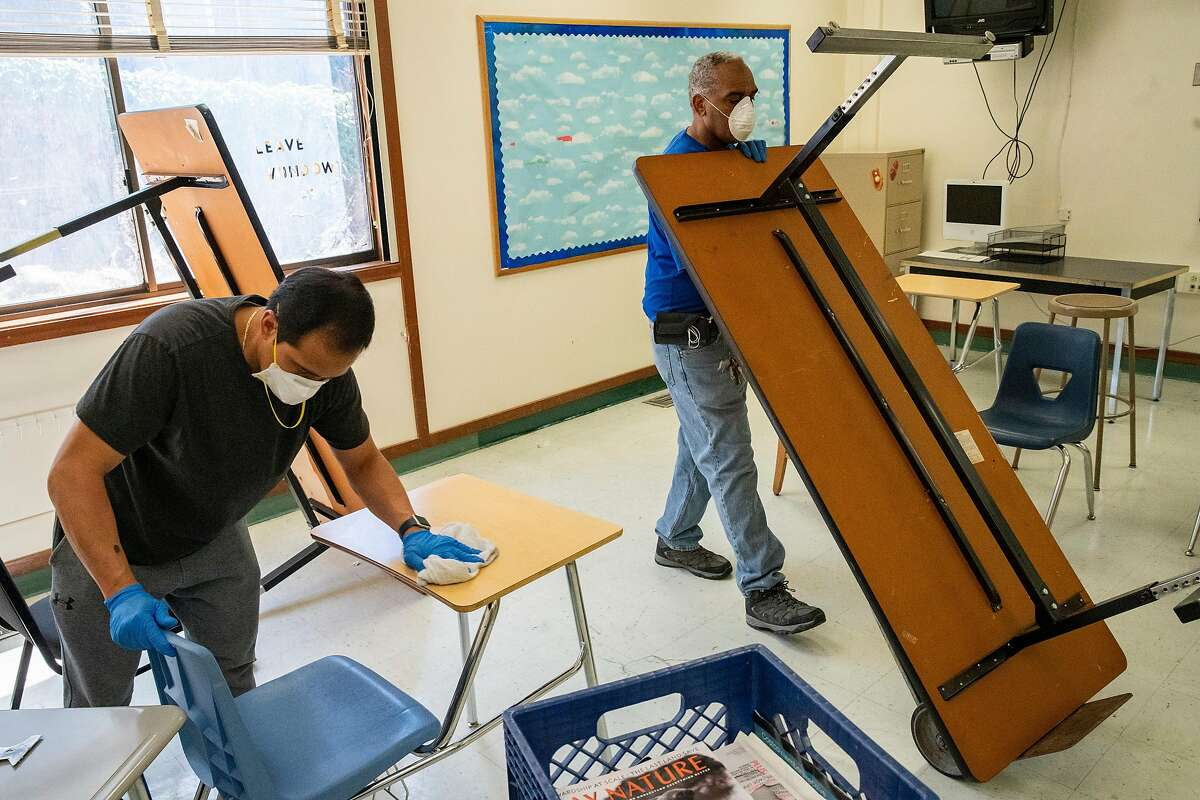 From left: Custodians Orlando Lavarias and Herman Flood clean and sanitize a classroom that will be set up for physical distancing at Westlake Middle School on Friday, July 10, 2020, in Oakland, Calif. Schools are planning on how to reopen in the fall to ensure the safety and wellbeing of students and staff, amid the coronavirus pandemic. The middle school also holds the MetWest High School Ericka Huggins Campus.