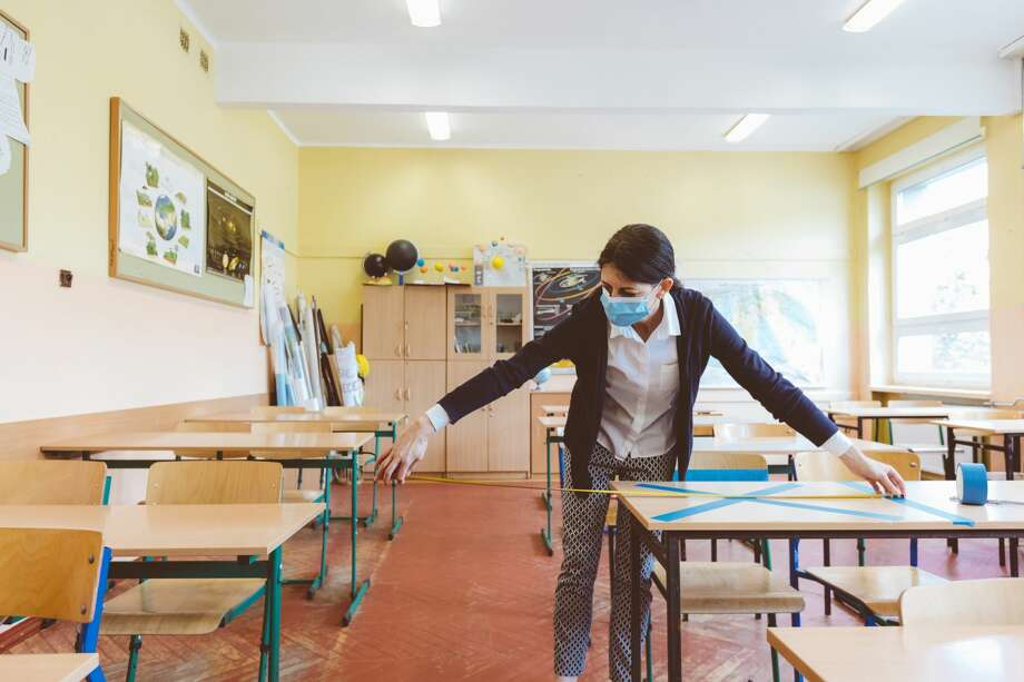 A teacher measures and marks places in the classroom that are to be empty after students return to school. Photo: Izusek