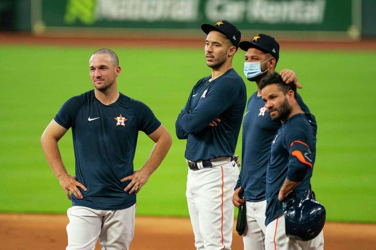 Houston Astros third baseman Alex Bregman (2), shortstop Carlos Correa (1), first baseman Yuli Gurriel (10) and second baseman Jose Altuve (27) listen to third base coach Gary Pettis during Astros summer training camp workout, Sunday, July 12, 2020, at Minute Maid Park in Houston.