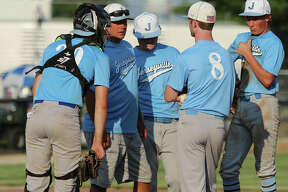 Jersey coach Darren Perdun (second left) talks with pitcher Nevan McDuffie (8) while teammates listen in during a mound visit in a game Wednesday at Ken Schell Field in Jerseyville.