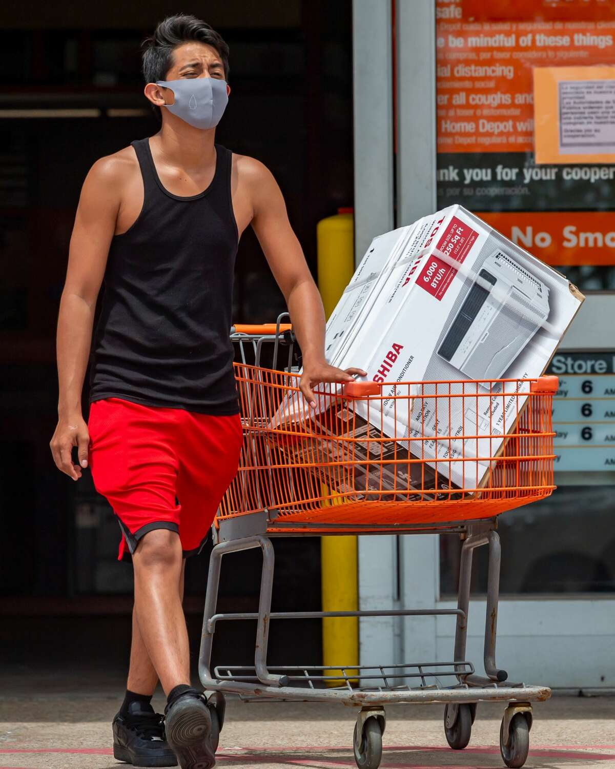 Jorge Sanchez walks out of the Home Depot in Beaumont on Sunday afternoon with a new window air conditioner to help him beat the heat at home. Photo made on July 12, 2020. Fran Ruchalski/The Enterprise
