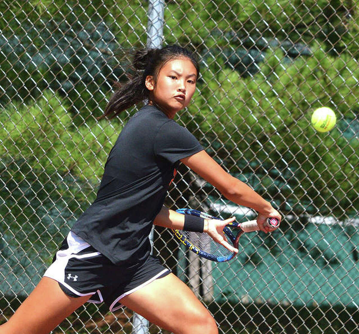 Edwardsville freshman Chloe Koons reaches for a shot on Saturday during her No. 1 singles match against New Trier 2 in the third-place match of the Heather Bradshaw Memorial Invitational.