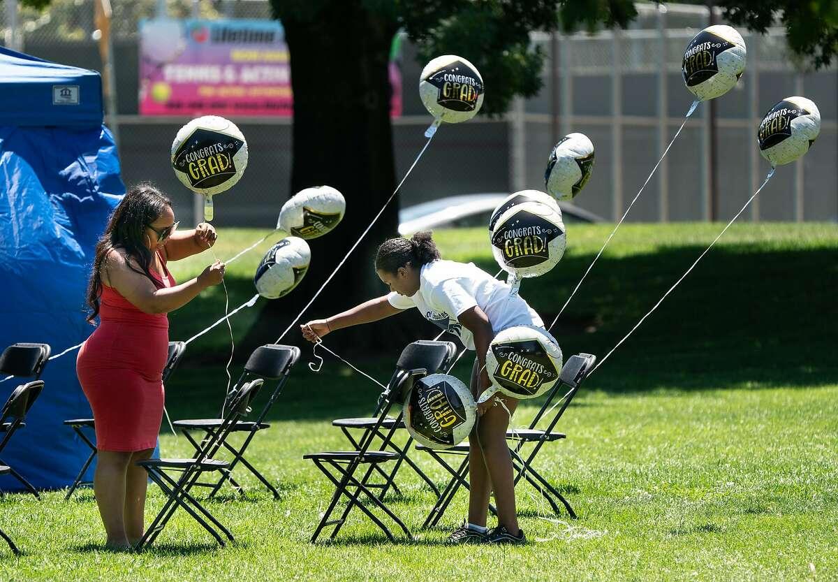 Kisha Merritt, left, and Chevon Jamerson set up balloons for a graduation celebration at Heather Farm Park as temperatures reach 100 degrees Fahrenheit on Sunday, July 12, 2020 in Walnut Creek, Calif.