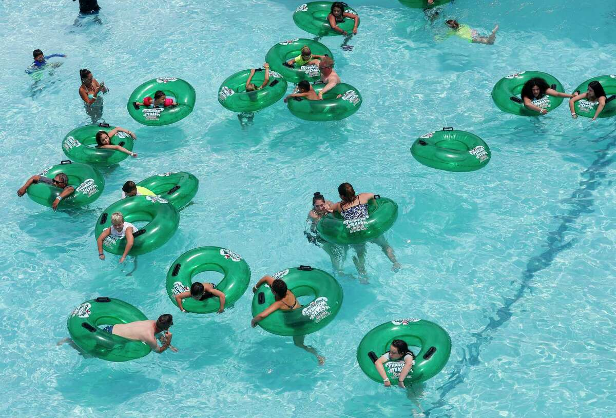 People seek refuge from the severe heat at Typhoon Texas Waterpark on Sunday, July 12, 2020, in Katy, Texas. The waterpark is operating at 25 percent occupancy because of the COVID-19 pandemic.