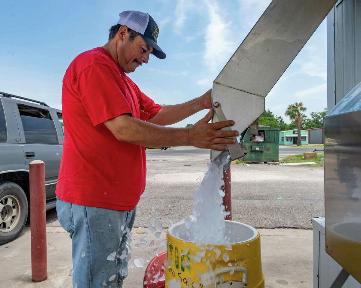 At one of the busiest places in Port Arthur, Gustavo Salcedo fills one of two coolers with bulk ice cubes from the Twice The Ice machine at 26th and Memorial Boulevard on Sunday. Photo made on July 12, 2020. Fran Ruchalski/The Enterprise