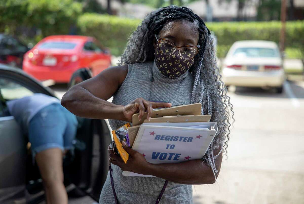 Andrea McWashington with Good Brothers & Sisters of Montgomery County the takes out a voter registration form in Conroe, Thursday, July 9, 2020.