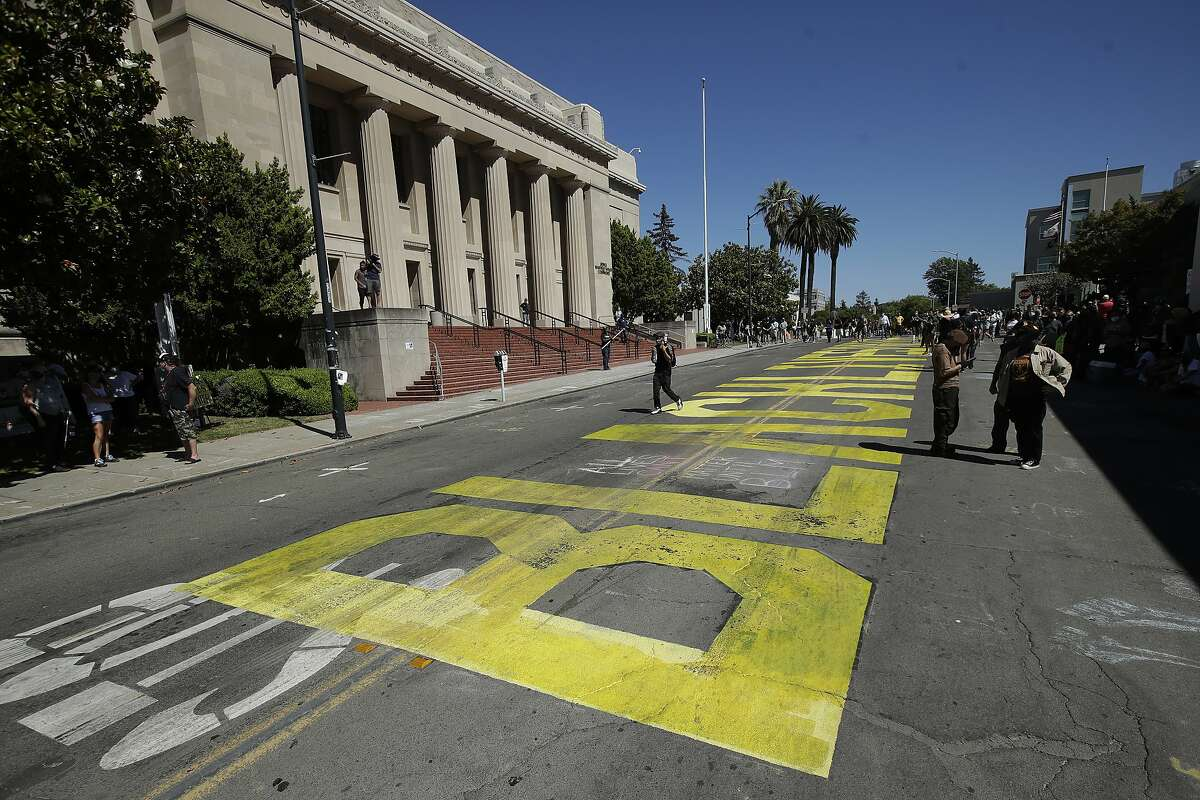 People walk past a Black Lives Matter mural written on a street in Martinez, Calif., Sunday, July 12, 2020, before a protest calling for an end to racial injustice and accountability for police. (AP Photo/Jeff Chiu)