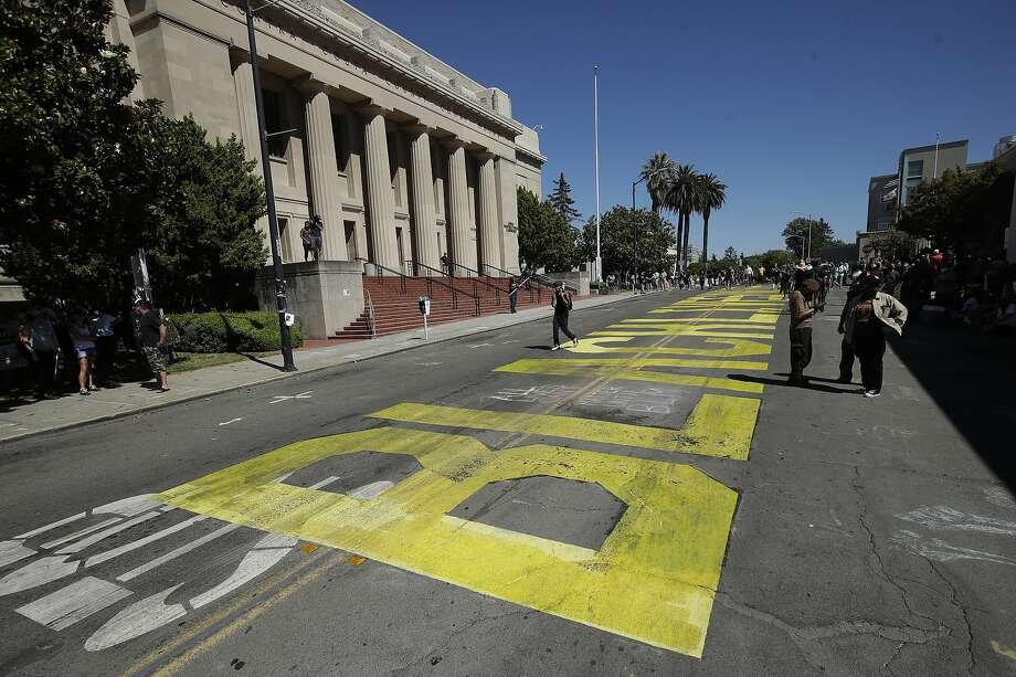People walk past a Black Lives Matter mural written on a street in Martinez, Calif., Sunday, July 12, 2020, before a protest calling for an end to racial injustice and accountability for police. (AP Photo/Jeff Chiu) Photo: Jeff Chiu, Associated Press