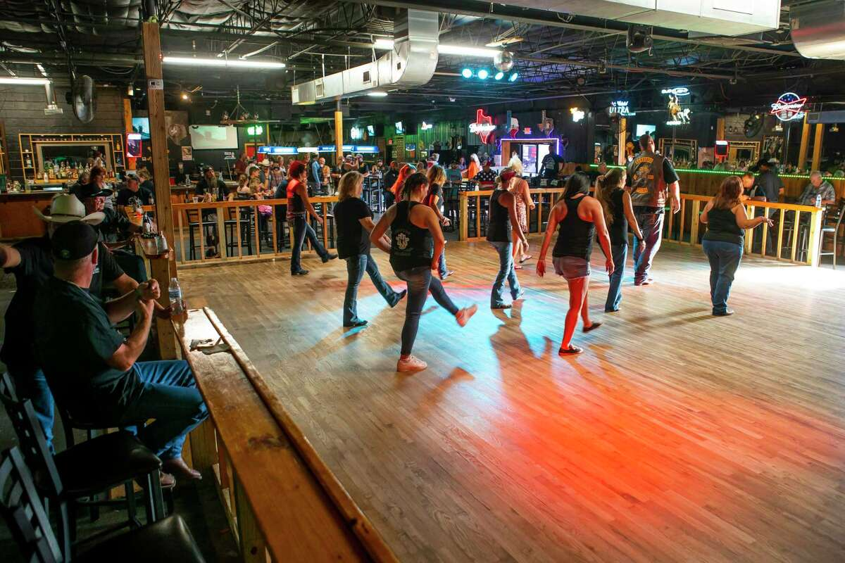 People line dance on July 12 at Chuters Dance Hall and Saloon in Pasadena. The bar opened in spite of Gov. Greg Abbott's order.