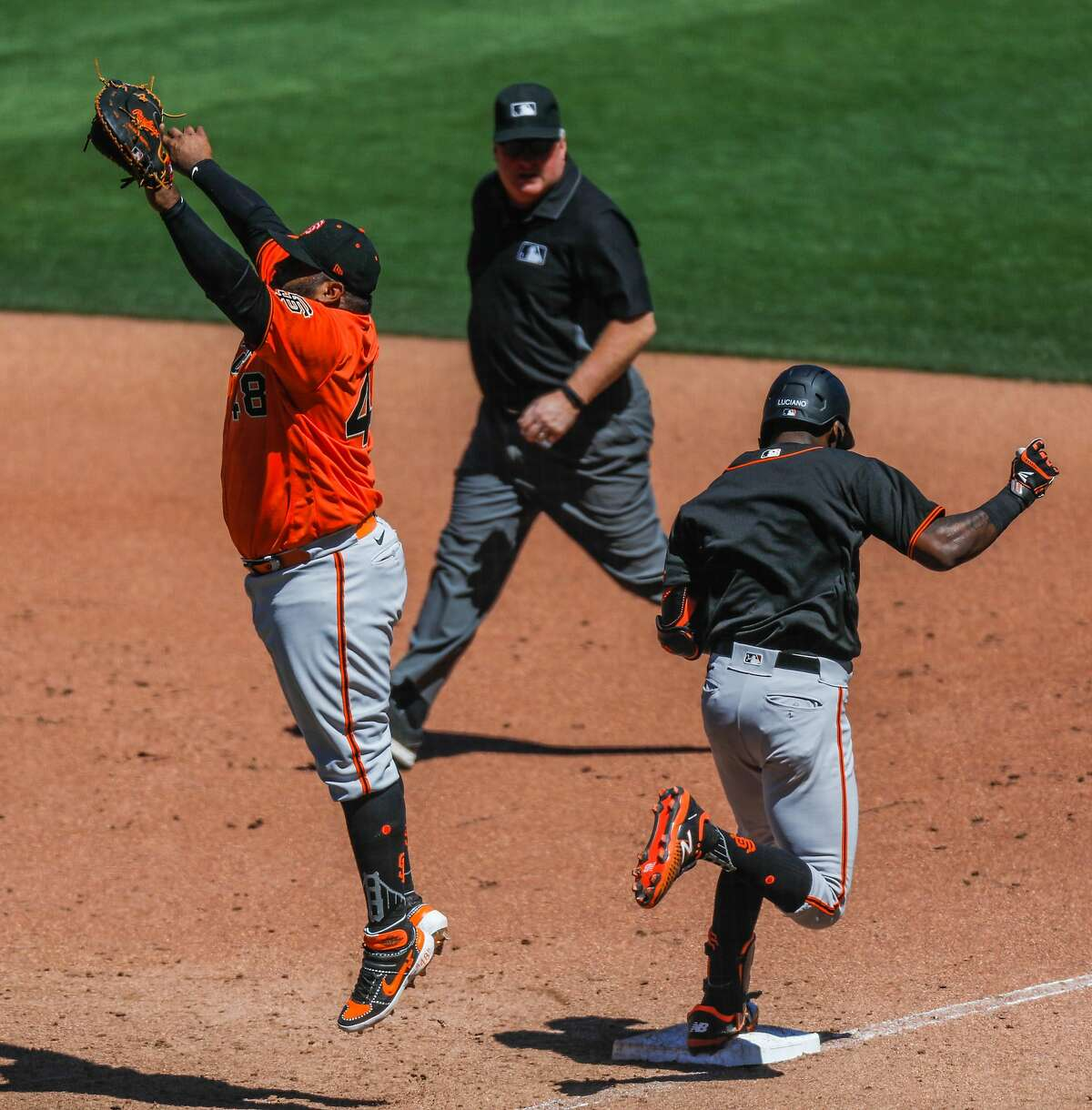 San Francisco Giants Pablo Sandoval reaches up to catch the ball as Marco Luciano (right) makes it to first base during Spring Training at Oracle Park on Sunday, July 12, 2020 in San Francisco, California.