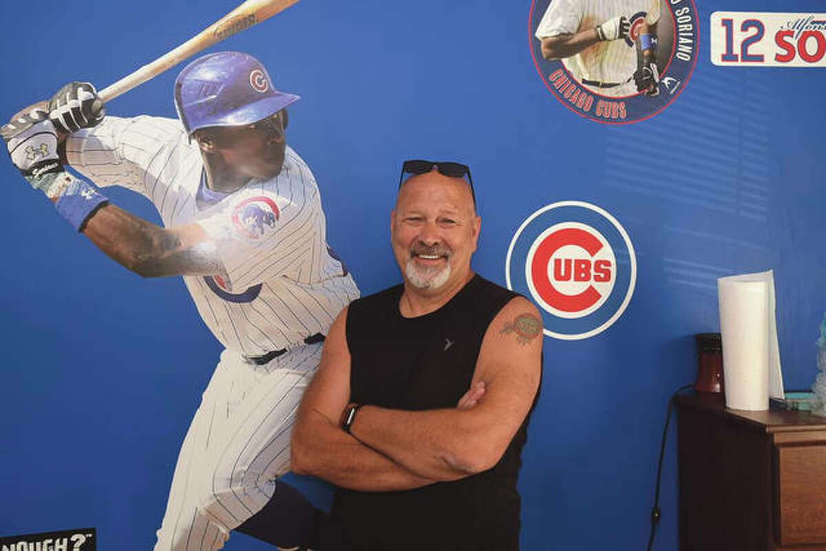 Dave Comstock at his Jacksonville residence, showing his sports team allegiance and sporting a Chicago Cubs tattoo.