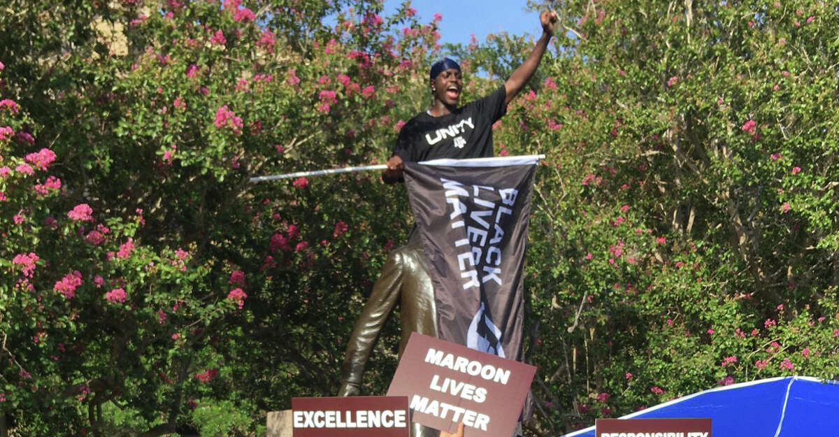 Texas A&M hurdler Infinite Tucker drapes a 'Black Lives Matter' flag over the head of the Sul Ross statue on the Texas A&M campus on Sunday evening.