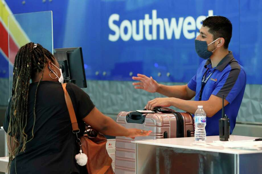 Southwest Airlines employee Oscar Gonzalez assists a passenger. Southwest is selling only 65 percent of its seats through Sept. 30 in order to keep the middle ones open. Photo: Tony Gutierrez /Associated Press / Copyright 2019 The Associated Press. All rights reserved.