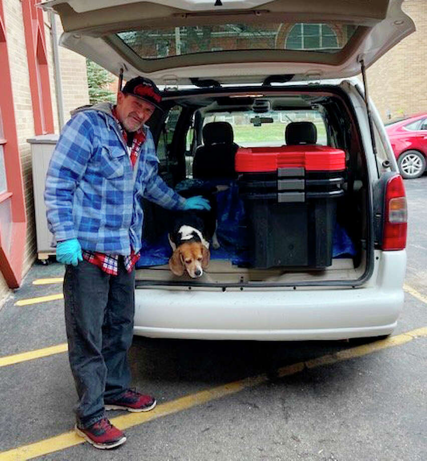 Michael Braden and his dog, Lucy, prepare to deliver meals to a distribution site in Mecosta County. Braden volunteers at Angels or Action, as well as donating time and items to other various local charitable organizations. Photo: Submitted Photo