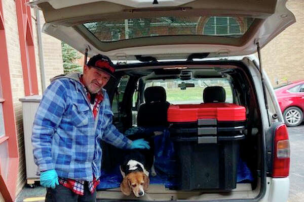 Michael Braden and his dog, Lucy, prepare to deliver meals to a distribution site in Mecosta County. Braden volunteers at Angels or Action, as well as donating time and items to other various local charitable organizations.