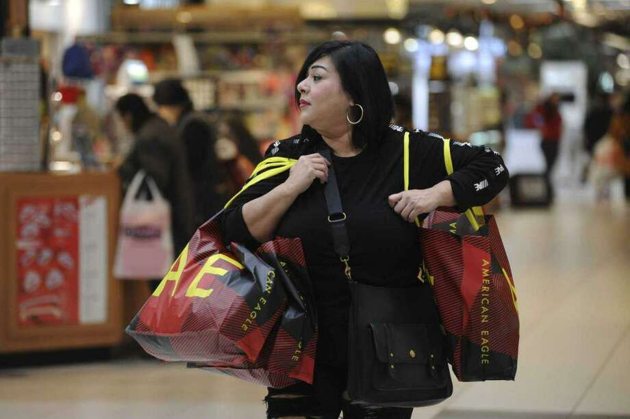 Anna Saldaña carries Christmas gift items purchased at American Eagle at South Park Mall on Black Friday, Nov. 29, 2019. Photo: Billy Calzada /Staff File Photo