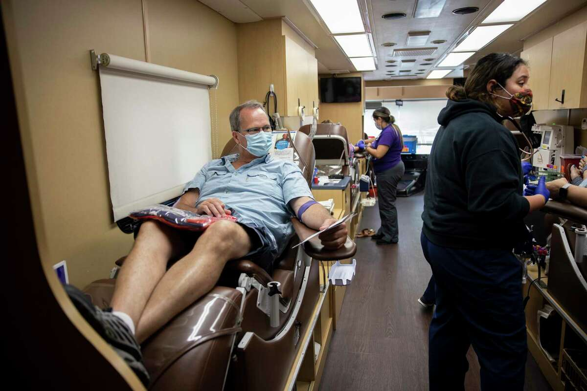 Gary Porter, left, watches as his wife begins to have blood drawn during a blood drive in The Woodlands, Sunday, July 12, 2020. The blood drive was held and hosted in front of Gringo's Mexican Kitchen.