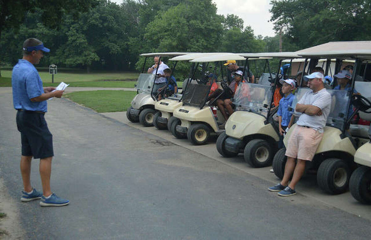 Mike Suhre, the head PGA golf professional at Oak Brook Golf Club, talks to golfers and parents on Tuesday night before the start of a PGA Junior Golf League match.