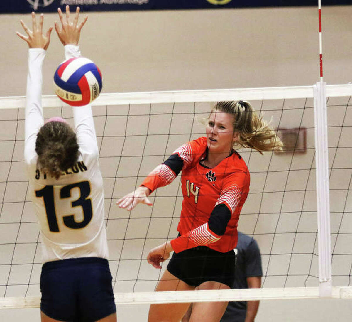 Edwardsville's Maddie Isringhausen hammers home a kill past the block of O'Fallon's Faith Mayfield (13) during a SWC match last season in O'Fallon.