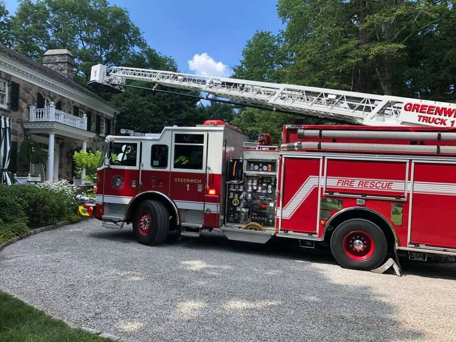 A ladder truck is brought into operation to work a garage fire in Glenville Sunday afternoon. Photo: / Greenwich Firefighters Union