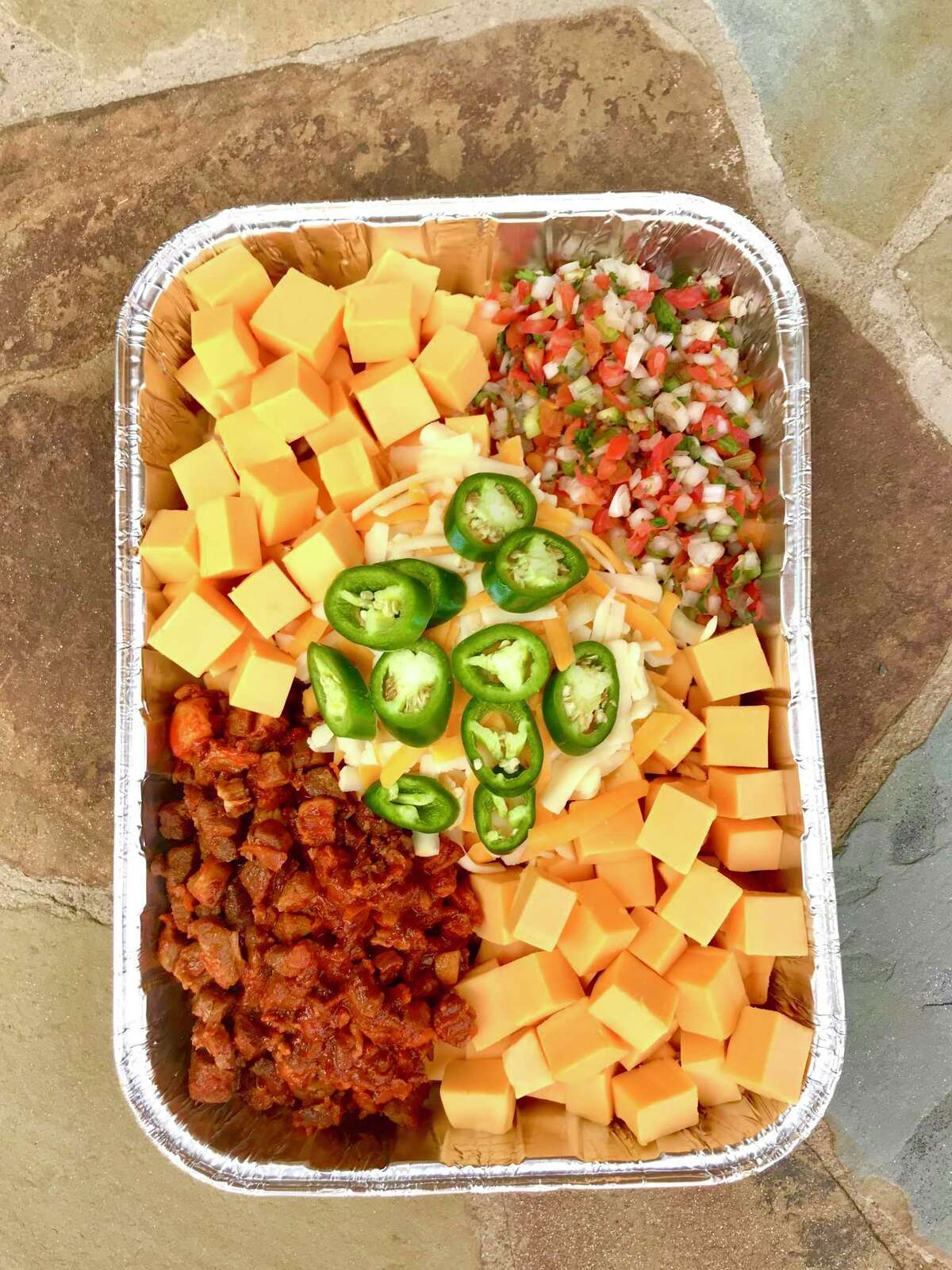 The smoked queso trend is simple: arrange ingredients for queso in a disposable aluminum pan or cast-iron skillet and place in a smoker or on the grill. Let the heat melt the queso.