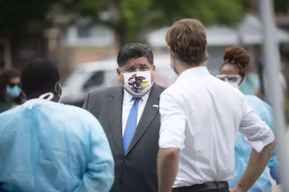 Gov. J.B. Pritzker masks up while talking with health officials.