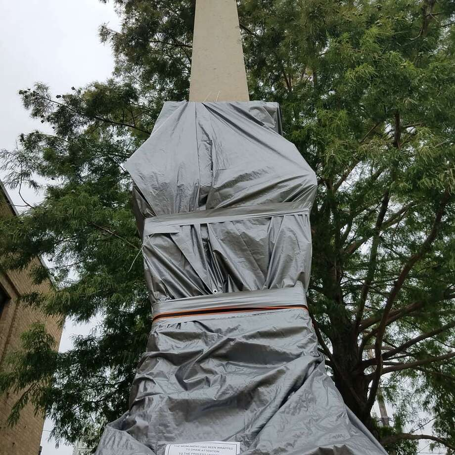 Activists pushing for the removal of the Jaybird-Woodpecker monument in Richmond, Texas have covered the statue in a tarp and erected a sign petitioning for its removal on July 12, 2020. Photo: Claire Goodman / Staff Writer