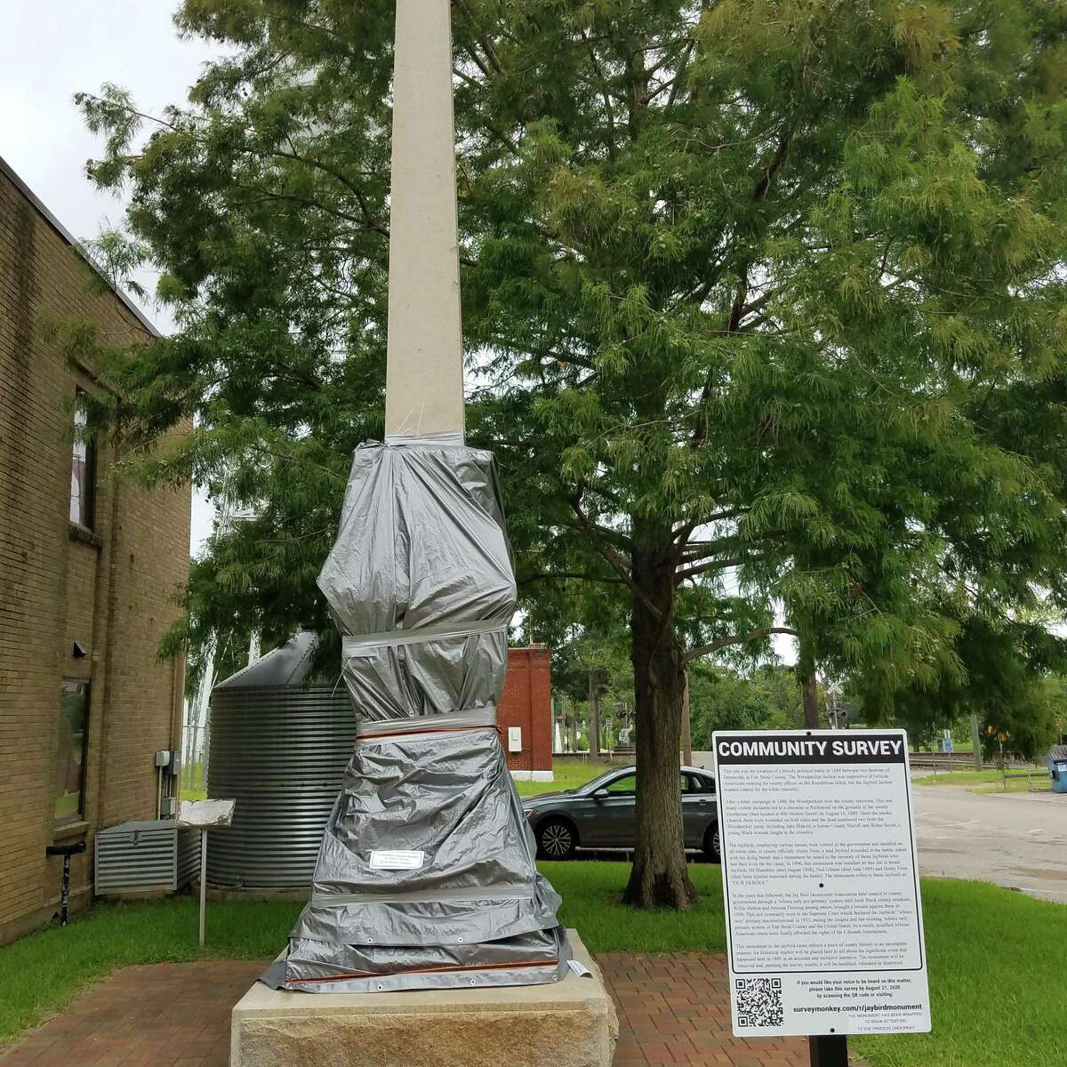 Activists pushing for the removal of the Jaybird monument in Richmond have covered the statue in a tarp and erected a sign petitioning for its removal.