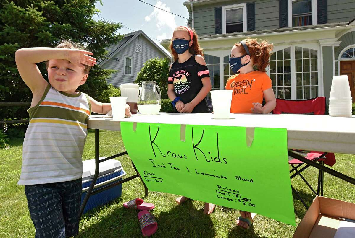 Patrick Kraus, 4, wipes his brow as he helps to sell lemonade and iced tea with his sisters Emma, 10, center, and Molly, 8, in front of their home on Monday, July 13, 2020 in Albany, N.Y. (Lori Van Buren/Times Union)