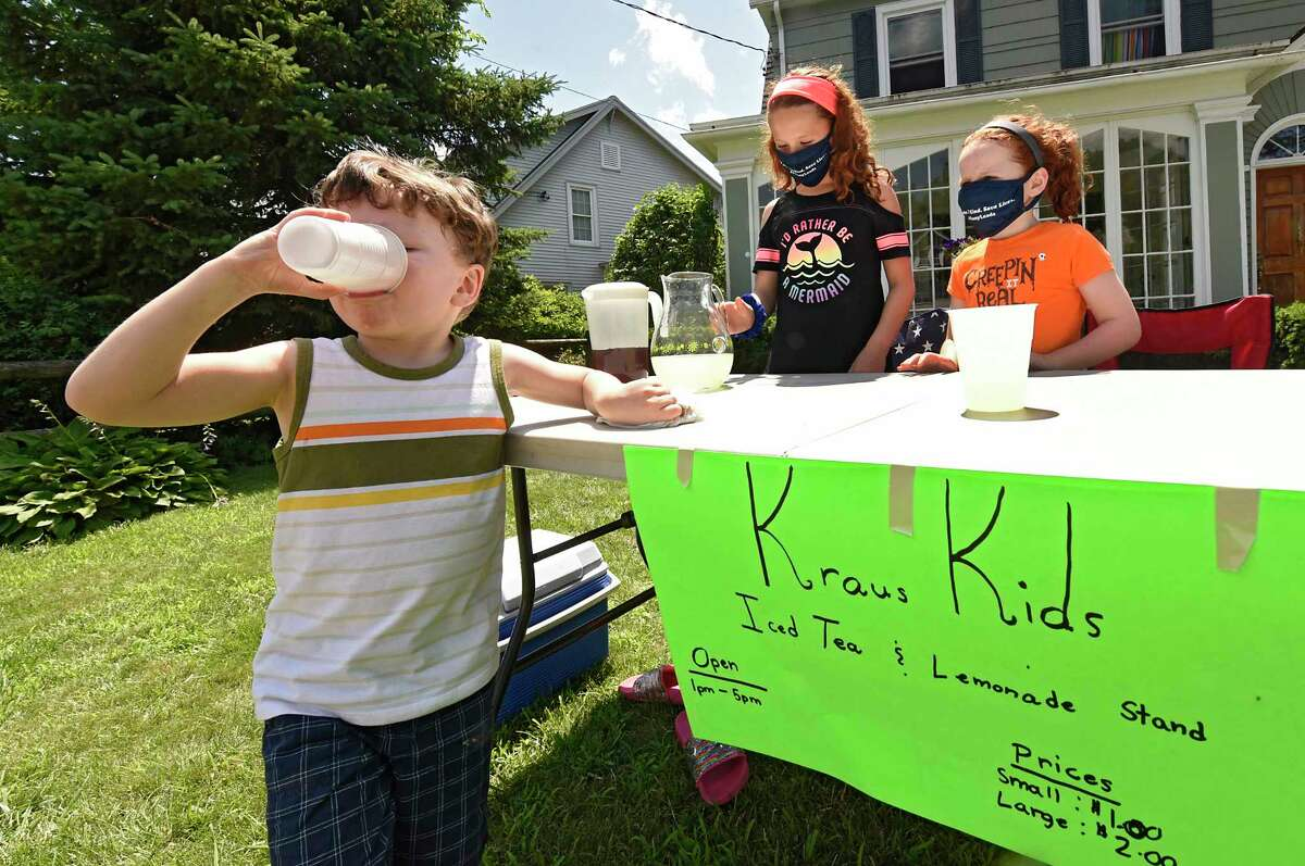Patrick Kraus, 4, taste tests the product as he helps to sell lemonade and iced tea with his sisters Emma, 10, center, and Molly, 8, in front of their home on Monday, July 13, 2020 in Albany, N.Y. (Lori Van Buren/Times Union)