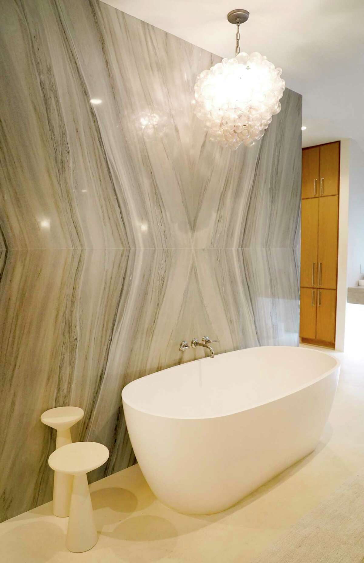 2. Statement wall: Bookmatched slabs of beautiful marble form a statement wall in this bathroom. On one side, it's a great backdrop for the freestanding bathtub and chandelier, on the other, it's a long wall for a huge shower. Wimmel Design and Construction did the massive remodel on this home that flooded in Hurricane Harvey.