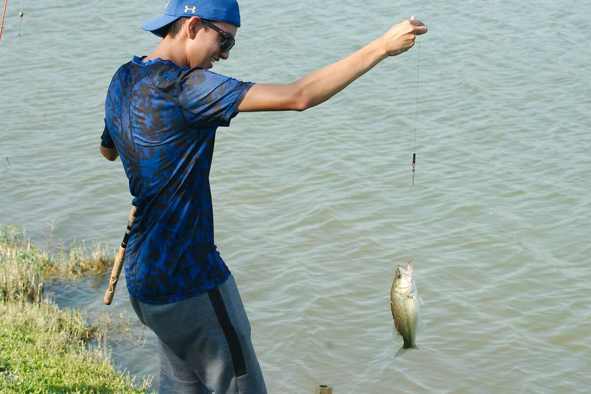 Christofer Sides reels in a nice largemouth bass at the lake at Edgewater Park in Webster.