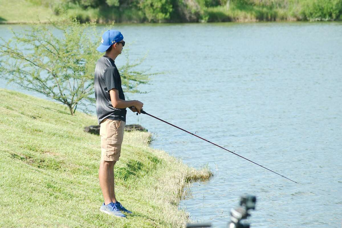 Christofer Sides spends the afternoon fishing at the lake at Edgewater Park in Webster.
