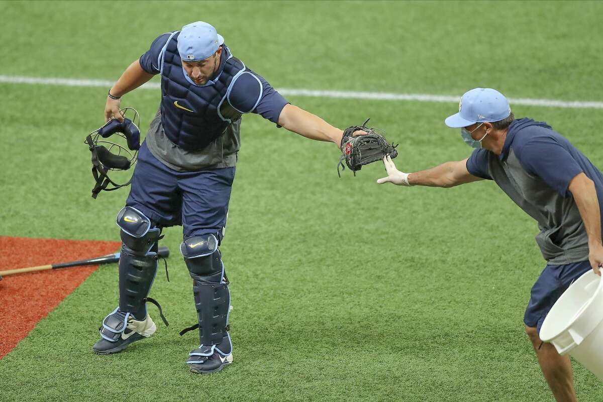 Tampa Bay Rays' Mike Zunino does a distant high five with coach Paul Hoover after a drill during baseball practice Saturday July 4, 2020, in St. Petersburg, Fla. (AP Photo/Mike Carlson)