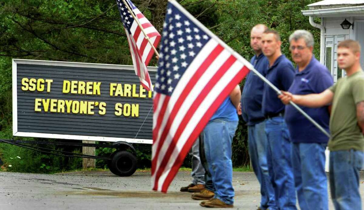 Mourners wait on the side of the road at Thoma Tire Company for the casket carrying the remains of Staff Sgt. Derek Farley in Schodack on August 25, 2010. (Skip Dickstein/Times Union)
