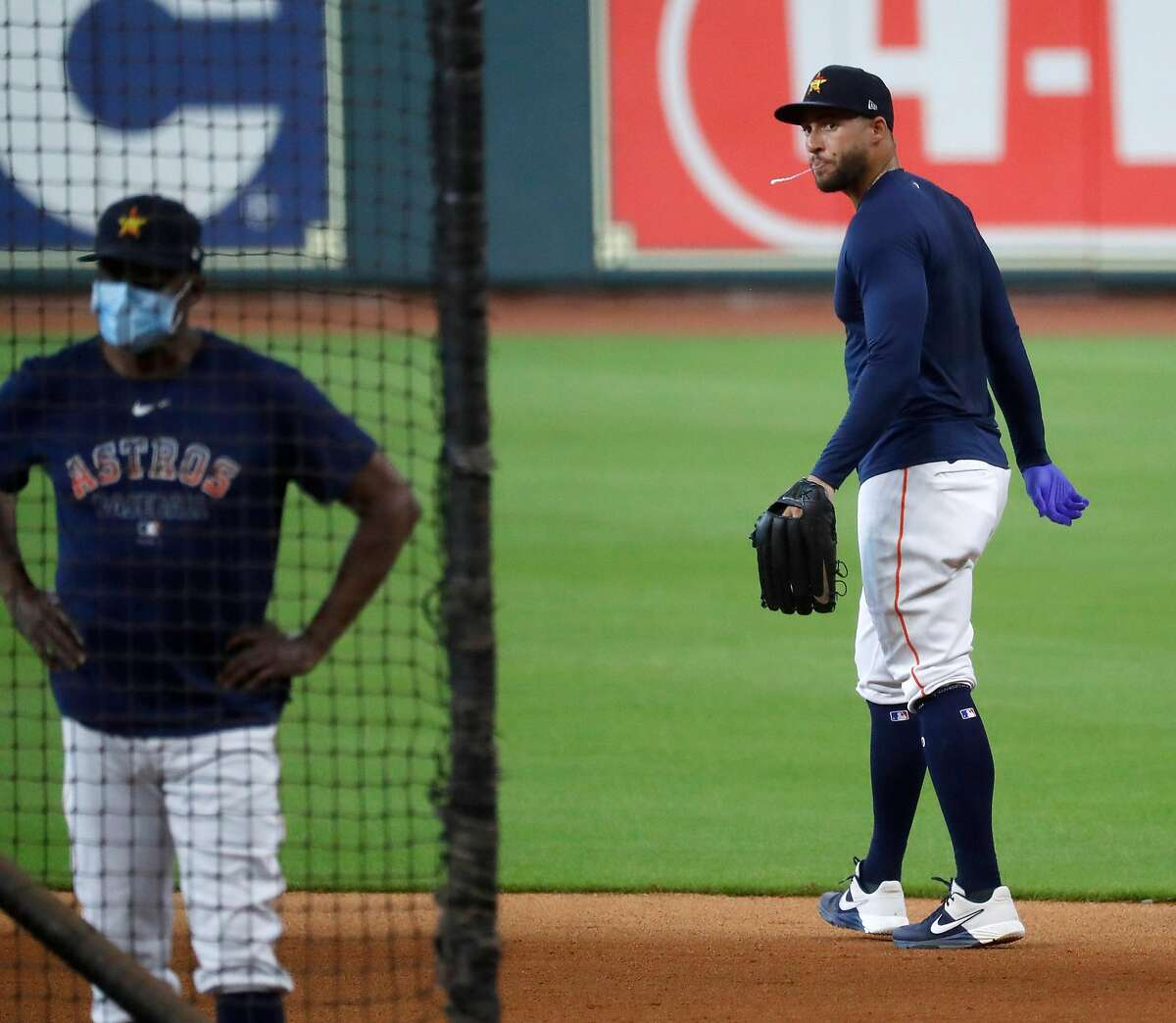 Houston Astros center fielder George Springer spits while wearing a latex glove as he prepared to go shag balls during the Astros summer camp at Minute Maid Park, Saturday, July 4, 2020, in Houston.