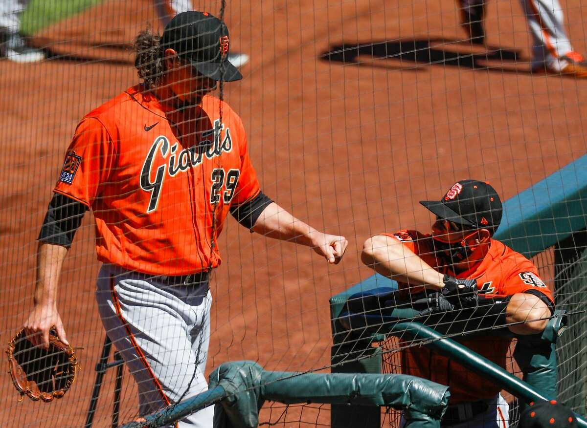 San Francisco Giants Jeff Samardzija (center) fist bumps a player in the dug out during Spring Training at Oracle Park on Sunday, July 12, 2020 in San Francisco, California.