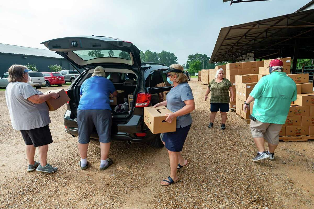 Volunteers at Harvest Church in Jasper load Farm to Family food boxes into a line of vehicles on Friday morning. Some were picking up several boxes and delivering them to family and neighbors who are also low on food. After several of Jasper County's food banks closed at the start of the coronavirus back in April, all five are up and running again. The demand still remains high and the Southeast Texas Food Bank is hoping the supply of produce increases.. Photo made on July 10, 2020. Fran Ruchalski/The Enterprise