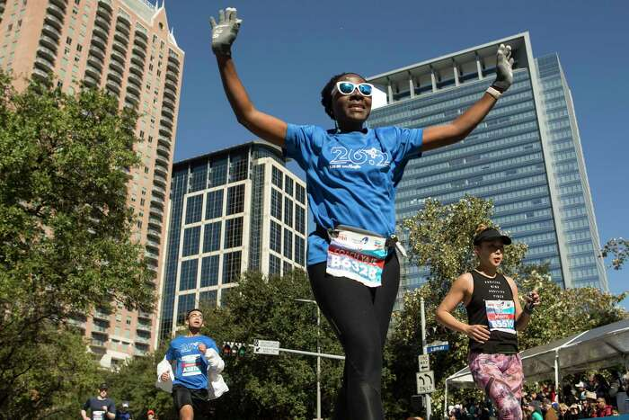 Yaje Ngala raises her arms as she kicks toward the finish line of the Chevron Houston Marathon Sunday, Jan. 19, 2020 in Houston.