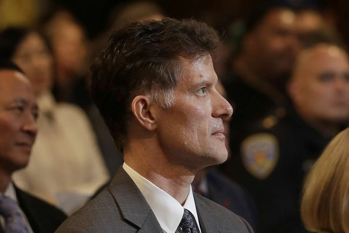 Grant Colfax, center, listens as San Francisco Mayor London Breed speaks during her state of the city address in San Francisco, Wednesday, Jan. 30, 2019. (AP Photo/Jeff Chiu)
