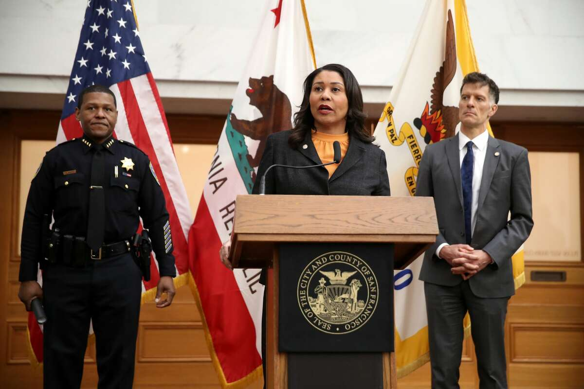 San Francisco Mayor London Breed, center, speaks during a press conference as San Francisco police Chief William Scott, left, and San Francisco Department of Public Health Director Dr. Grant Colfax look on at San Francisco City Hall on March 16, 2020, in San Francisco.