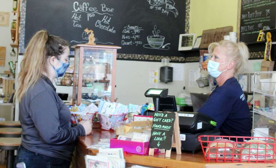 A customer wearing a face mask orders a meal to-go Monday at the Yellow Window in downtown Big Rapids. Gov. Gretchen Whitmer, last week, mandated that Michigan businesses open to the public deny service or entry to customers who refuse to wear one starting Monday. Photo: Pioneer Photo/Catherine Sweeney